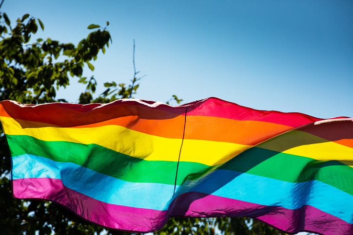 Low Angle View Of Rainbow Flag Waving Against Clear Blue Sky