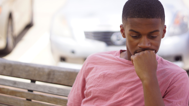 Close-Up Of Thoughtful Man Sitting On Bench