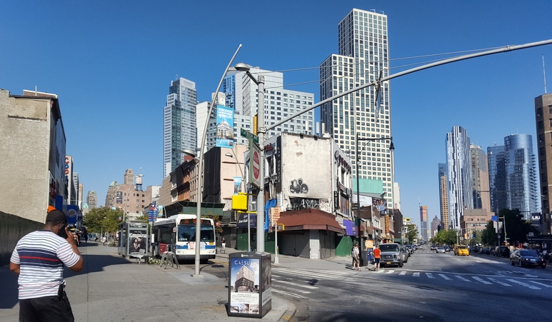 Man walking while holding a cell phone between Fulton Street and Flatbush Avenue in Downtown Brooklyn, New York City