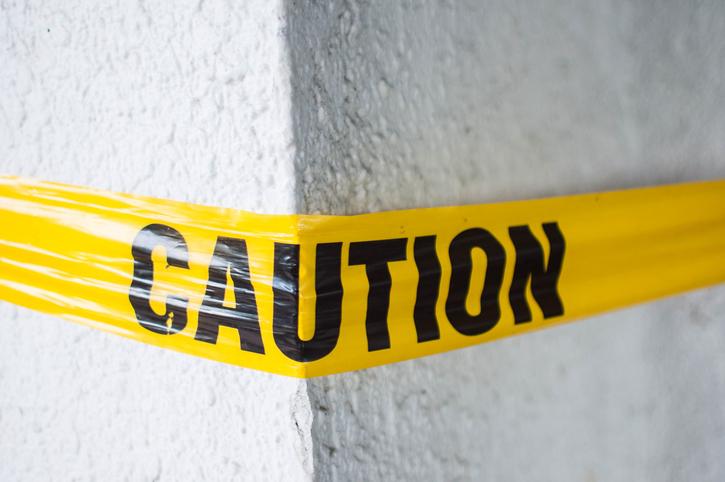 A yellow plastic cordon tape caution warning sign