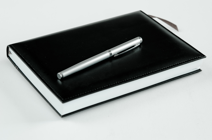 High Angle View Of Book With Pen On White Background