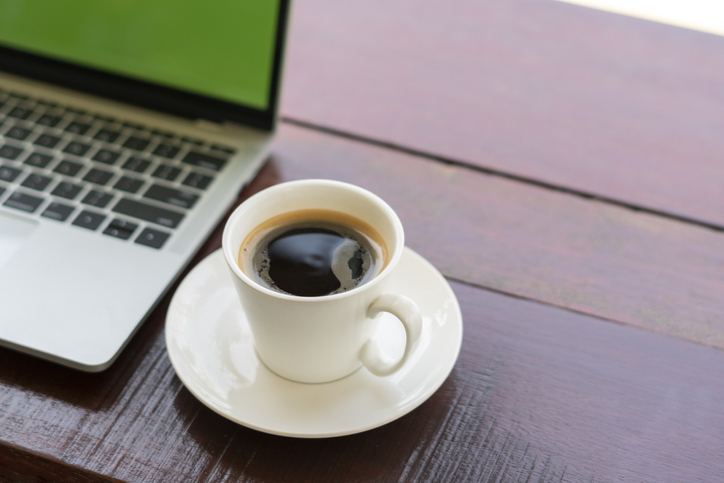 white coffee cup on wooden table beside laptop computer.