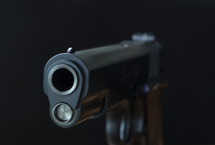 close up pistol gun barrel and wooden and dark black ground