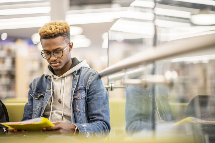 An African American University Student Studying in the Library stock photo