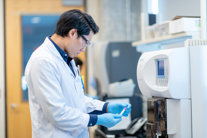 Asian Scientist Checking a Vial Before Processing it in the Equipment stock photo