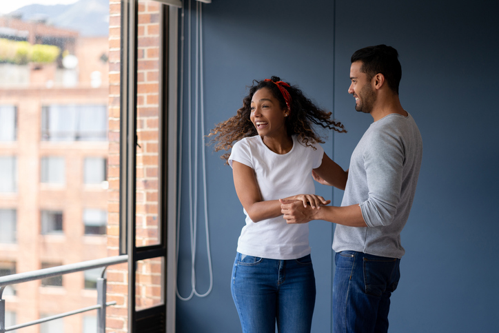 Excited couple looking very happy at their new house