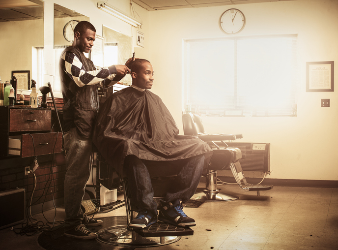 Barber in traditional barber shop shaving man's head
