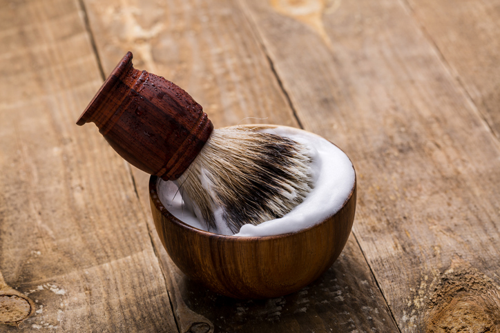 Shaving brush and bowl on table. Shaving accessories