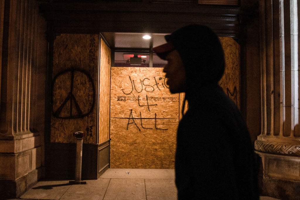 A protester walks past justice 4 all graffiti outside the...