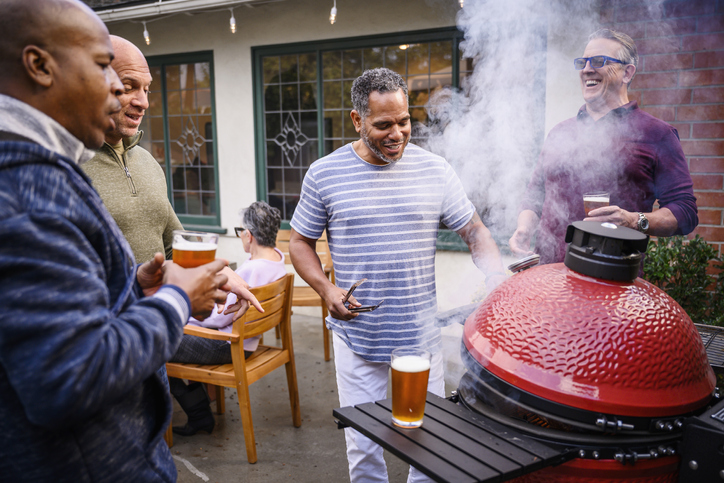 Mature men standing by barbecue grill talking
