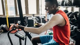 One young man volleyball player training on exercise bike