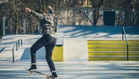 Skateboarder sliding on a rail in the skatepark