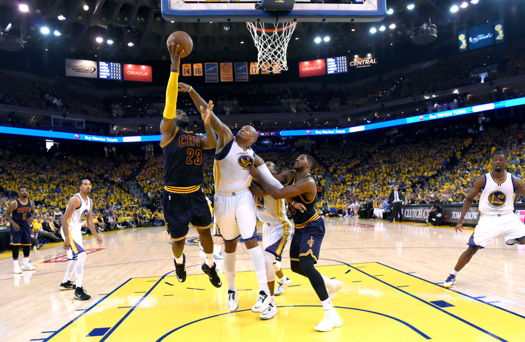 From left, Cleveland Cavaliers' LeBron James (23) tries to make a basket as Golden State Warriors' Marreese Speights (5) blocks and Warriors' Andre Iguodala (9) gets blocked by Cleveland Cavaliers' Tristan Thompson (13) in the second quarter of Game 2 of