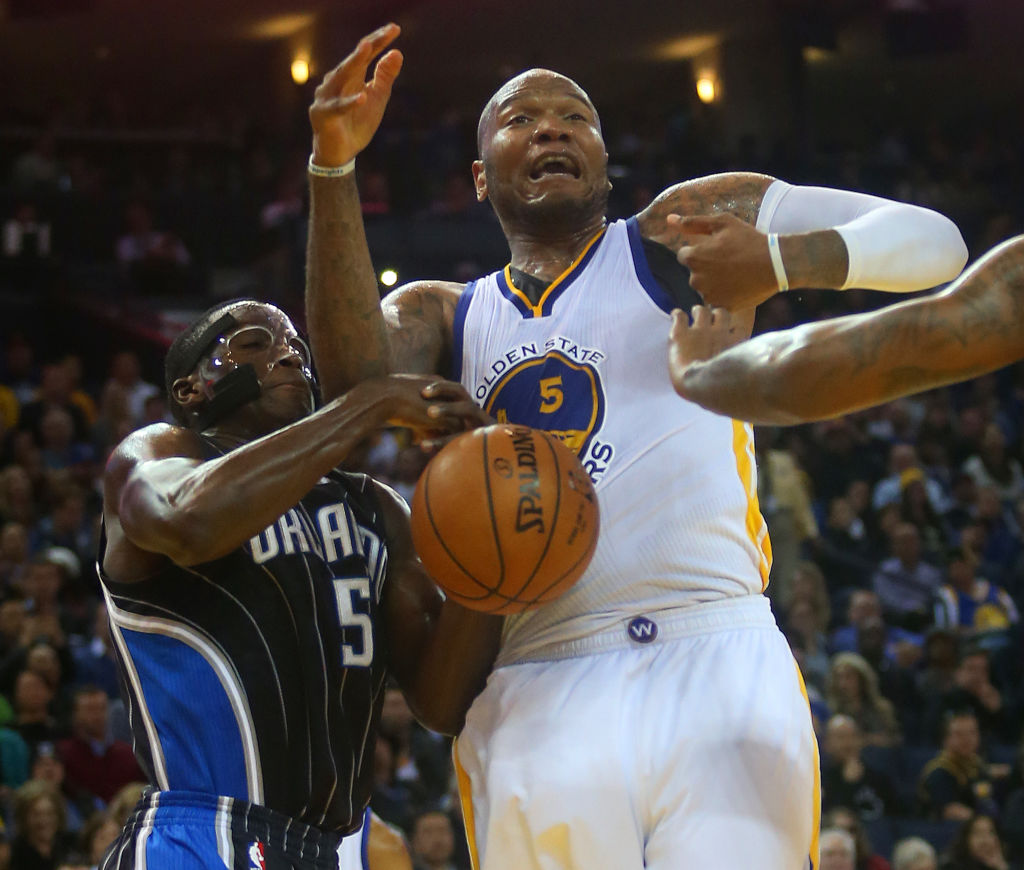 Golden State Warriors forward Marreese Speights (5) battles the Orlando Magic's Victor Oladipo (5) for a loose ball during their game on Tuesday, Dec. 2, 2014 in Oakland, Calif. (Aric Crabb/Bay Area News Group)