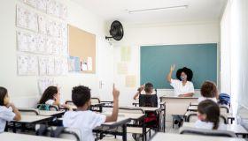 Teacher teaching in classroom respecting social distancing between students
