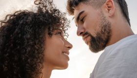 Close-Up Of Couple Embracing While Standing Against Sky