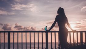 Silhouette of sensual woman drinking blue lagoon cocktail on tropical balcony at sunset.