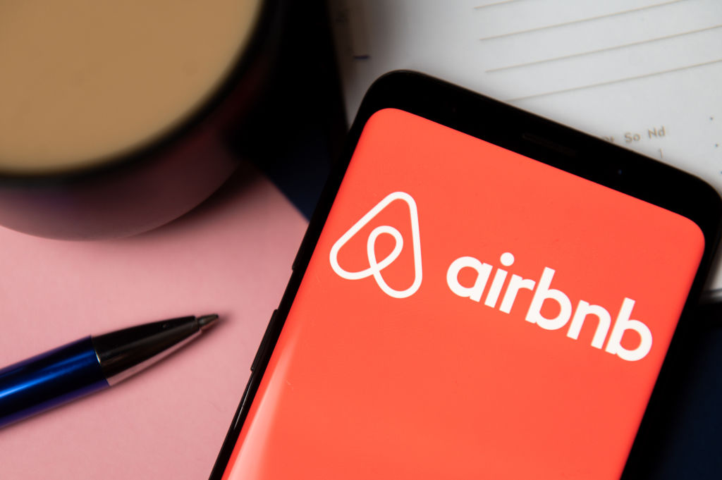 In this photo illustration Airbnb logo displayed on a...