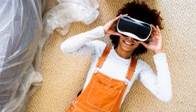 Afro woman wearing virtual reality simulator while lying on carpet in new apartment