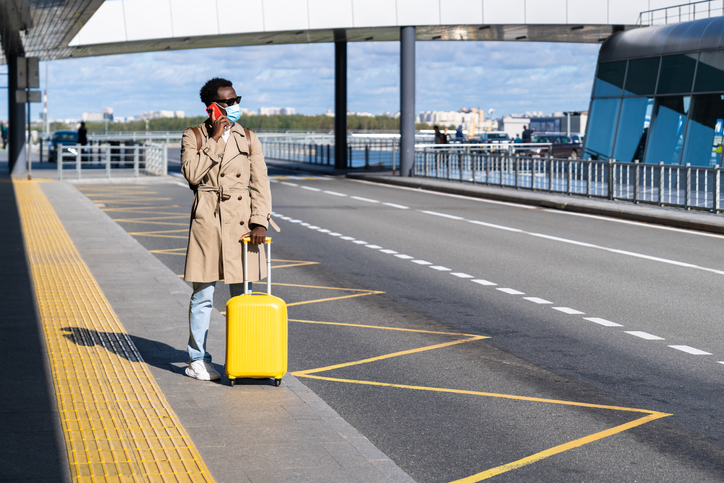 Man With Suitcase Talking Over Phone While Standing On Road At Airport