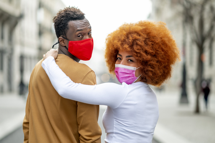 Woman wearing face mask with arm around on man standing outdoors