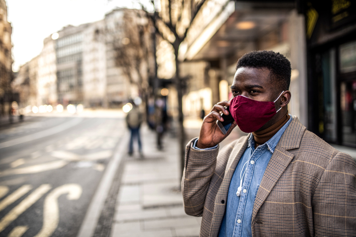 African American man waiting for a bus in the city with face mask on.