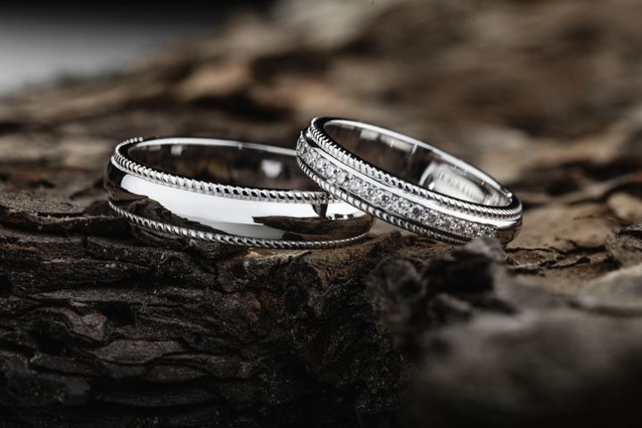 Pair of stylish silver wedding rings on wood background