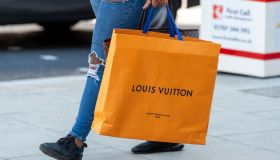 A shopper carries a Louis Vuitton shopping bag on Londons...
