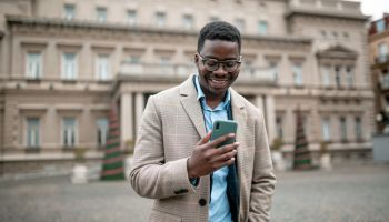 Happy young African American businessman using a smart phone