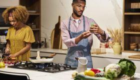 Man Examining Ingredient Bottle While Cooking