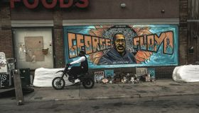 A man rides a motorcycle next to a mural of George Floyd by...