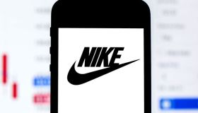 In this photo illustration a Nike logo seen displayed on a...