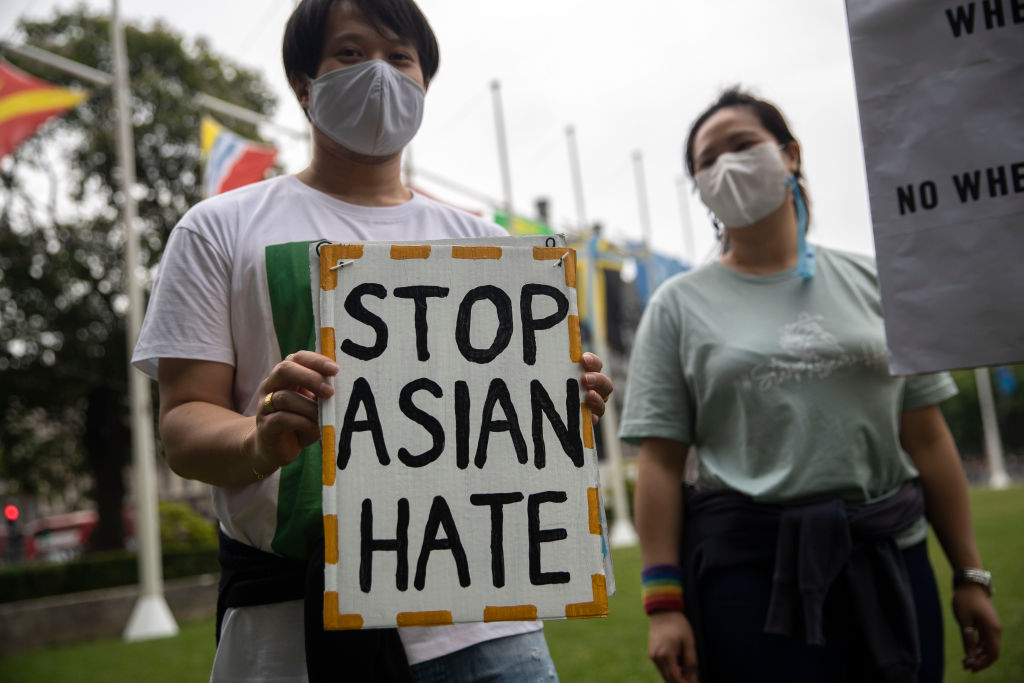 Protesters hold placards outside Parliament Square during...