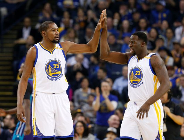 Golden State Warriors' Kevin Durant (35) high-fives Golden State Warriors' Draymond Green (23) during their game against the Charlotte Hornets in the first quarter at Oracle Arena in Oakland, Calif. on Wednesday, Feb. 1, 2017. (Nhat V. Meyer/Bay Area News