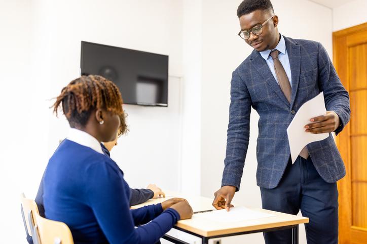 High School African - American teacher distributing a school exam