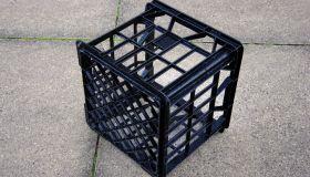 Black plastic milk crate on a concrete sidewalk