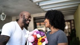 Husband surprising his wife with a flowers and present at home